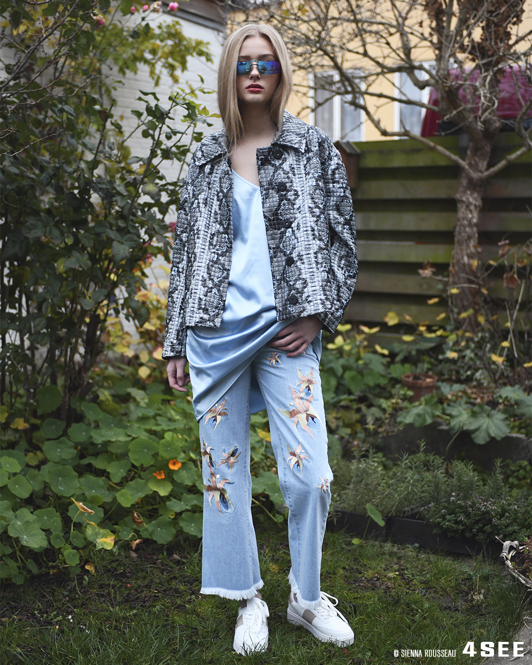 Scandi-Savvy features Prada's blue mirrored skinny sports sunglasses. A female blonde model wears a sneak skin jacket by Stand, with blue inner and jeans by Blanche